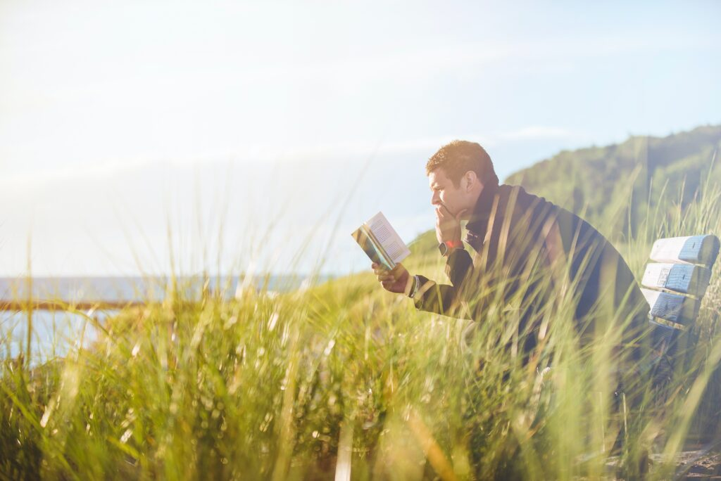 Person on beach, clothed, reading a book