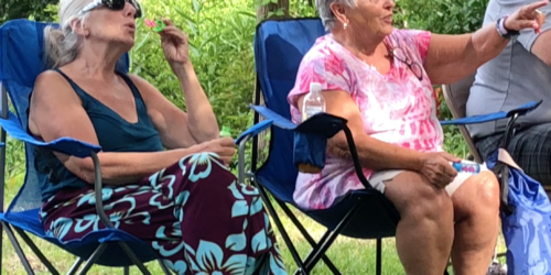 two people blowing bubbles and laughing
