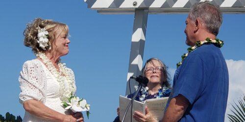 Reverend Kathy in Wedding dress, flowers in her hair, facing Don Shinnaman in blue shirt